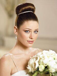 Búi tóc cô dâu đỉnh đầu giúp gương mặt thanh thoát.